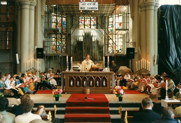 April 1997: Eerste H. Communieviering tijdens de restauratiewerkzaamheden. Het hoogaltaar is beschermd door doorzichtig plastic. Rechts staat het orgel nog, ingepakt met zwart plastic. Het orgel heeft op deze plaats gestaan van 1970 tot 1998. Tijdens de restauratie werd het orgel op het oksaal geplaatst.