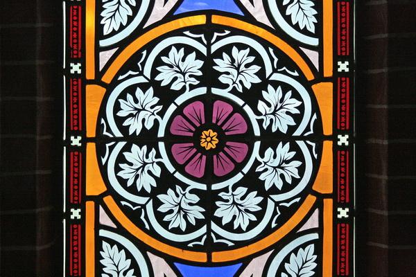Detail van een raam dat in 1998 werd aangebracht. De decoratieve elementen van de eind 19e eeuwse ramen (geheel links en rechts in de apsis) dienden als voorbeeld. De eind 19e eeuwse ramen hebben hetzelfde patroon: rozetten, kleine blauwe segmenten erboven en eronder en vier halfronde okergele bogen als omsluiting. Een rode bies volgt de rand van het raam.