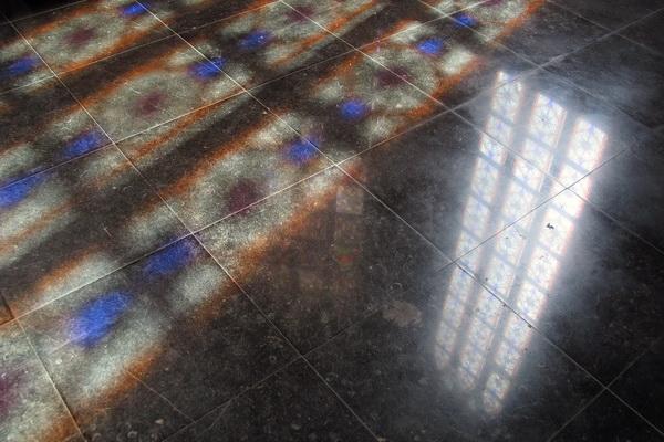 De middagzon weerspiegelt zich, op welhaast meditatieve wijze, in de vloer van het priesterkoor.